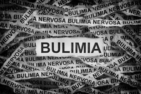 Bulimia. Torn pieces of paper with the word Bulimia. Concept Image. Black and white. Close up. Stock Photo