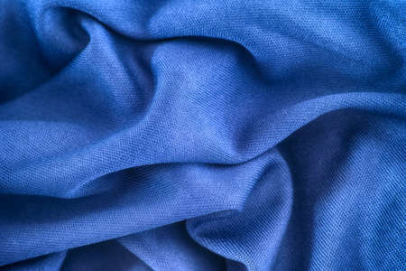 Blue wrinkled fabric texture background. Close up.