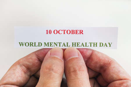 Person holding piece of paper with the words World Mental Health Day (10 October). Close up. Stock Photo