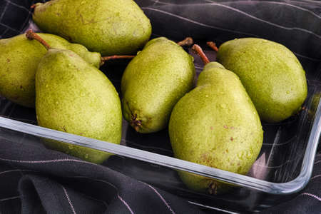 Green pears in a glass container. Close up.