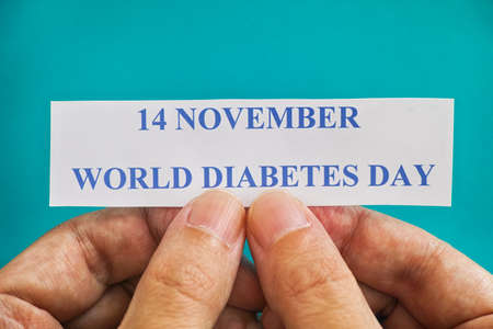 Person holding piece of paper with the words World Diabetes Day (14 November). Close up.