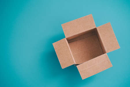 Open cardboard box on a blue background. Stock Photo