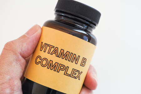 Person holding a bottle of Vitamin B Complex. Close up.