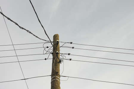 An old electric wooden pole with electricity cables hanging on it. Natural light.