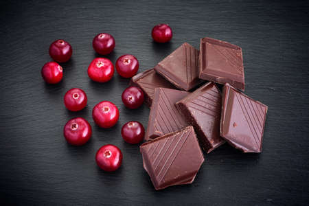 Cranberry with pieces of broken chocolate. Low key. Close up. Stock Photo