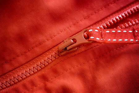 Closeup shot of a zipper on a red jacket. Close up. Stock Photo