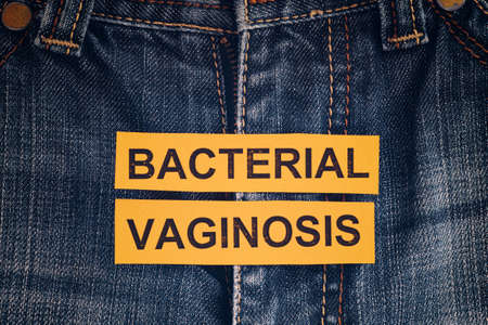 Yellow pieces of paper with the words Bacterial Vaginosis. Close up. Stock Photo