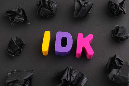 The abbreviation IDK (I don't know) made out of polymer clay letters with some black crumpled paper balls around it. Low key. Close up. Imagens
