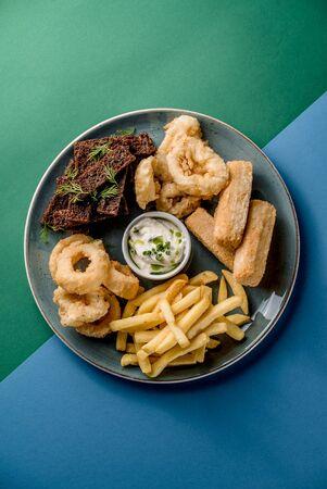 Plate snacks deep frying toast french fries squid tempura bar top view Фото со стока