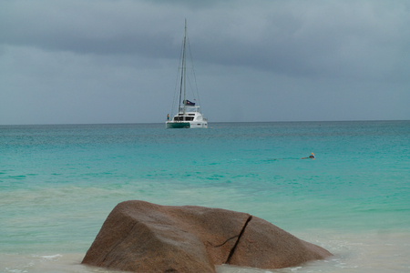 argent: Snorkler in front of a Catamaran at anchor in the Seychelles Islands Stock Photo