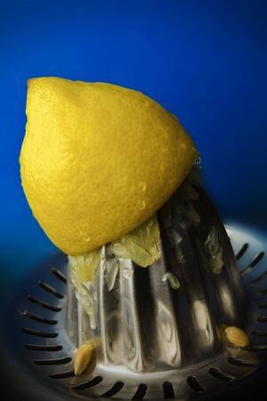 Yellow lemon being squeezed on a blue background. photo