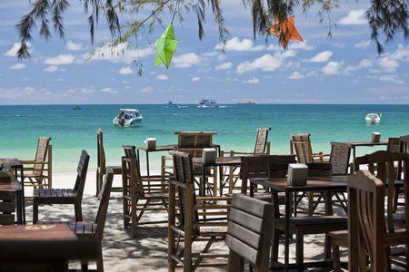 exotism: Restaurant tables on a white sand beach.