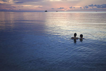 exotism: Couple having a bath in the ocean at sunset. Thailand.
