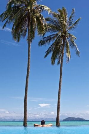 exotism: Man watching the ocean from a swimming pool . Ko phi phi island.