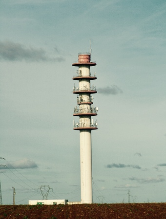 Telecommunications tower with its relay antennas and parables on vintage background