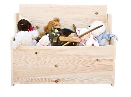Various toys in a hand crafted toy box isolated on white background.