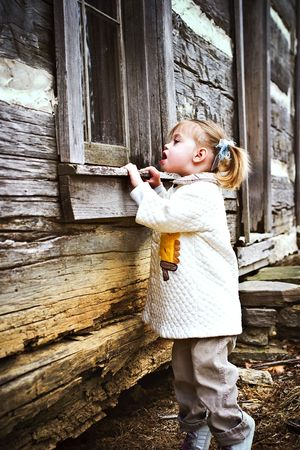 snooping: Curious toddler looking inside an old log cabin Stock Photo