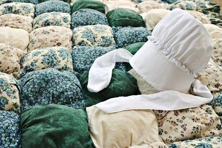 amish: Amish bonnet on a biscuit quilt