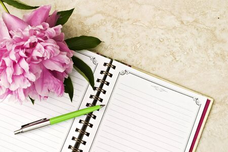 Notebook with pen and flowers photo