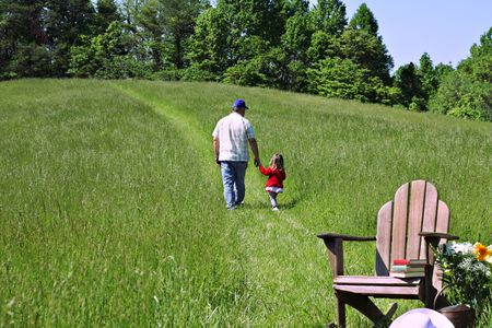 adirondack chair: A father and his daughter walking together in a beautiful field. Stock Photo