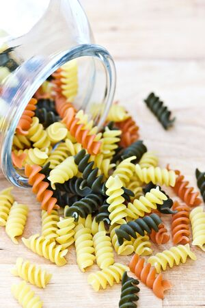 Tri colored rotini pasta spilling from a glass jar. photo