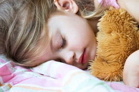 Toddler sleeping with her teddy bear photo