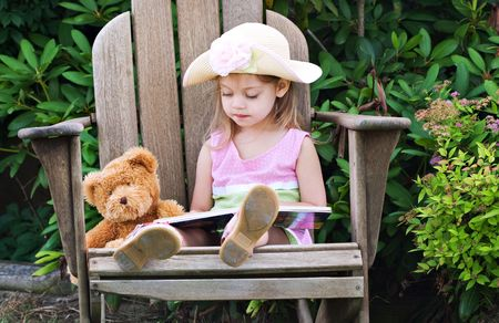 storytime: Little girl pretending to read to her teddy bear