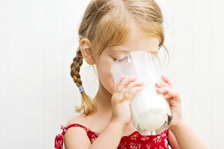 pasteurized: Cute little girl drinking a large glass of milk