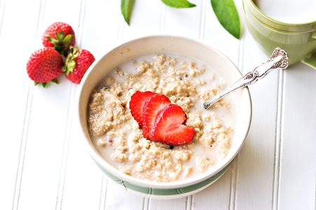 porridge: A bowl of hot oatmeal with fresh strawberries cut into the shapes of hearts for a heart healthy breakfast with a cup of milk. Shallow DOF.