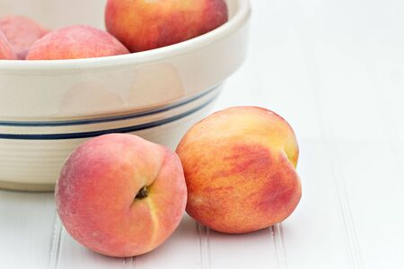 Fresh peaches by an antique bowl photo