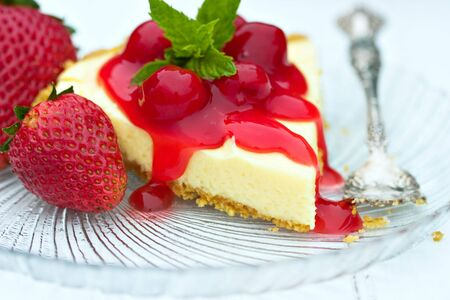 Luscious cheese cake with cherry sauce, mint and fresh strawberries. Stock Photo