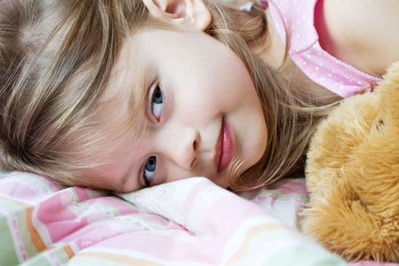 close up eyes: Toddler lying in bed with her teddy bear