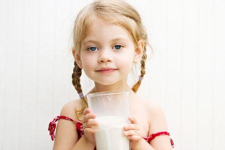 우유 콧수염과 우유의 큰 잔을 마시는 귀여운 소녀