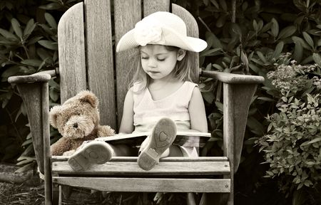 Vintage style image of a child reading to her teddy bear