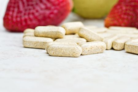 Prenatal vitamins with fresh fruit in the background. Shallow DOF with focus on front vitamin.