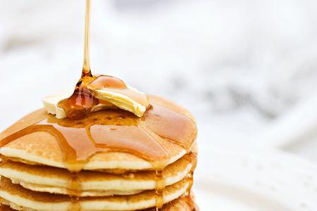 Ahorn suikerstroop pompen naar pancakes. Ondiepe DOF met focus op siroop en boter.