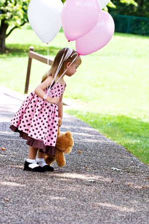 Little girl at a park with pink and white balloons and a little brown teddy.