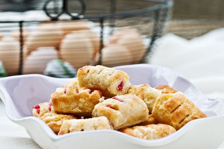 danish puff pastry: Assorted apple and cherry pastries in a lavender dish with fresh eggs in the background. Extreme shallow DOF with focus on pastries.