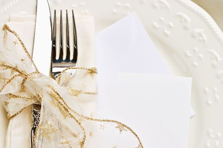 christmas catering: Holiday place setting with napkin, fork and knife tied with a gold ribbon. Blank card included. Stock Photo