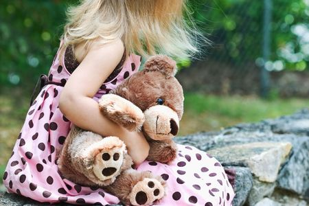 Little girl clutching her teddy bear as she waits for someone to pick her up. photo