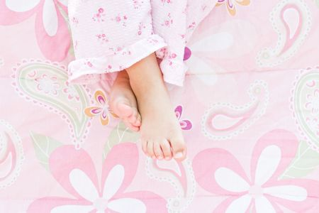 big toe: Little girls feet hanging over the edge of the bed. Stock Photo