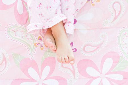 Meisje voeten opknoping over de rand van het bed. Stockfoto