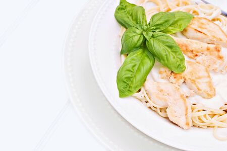 Chicken alfredo with basil on a white beadboard  photo