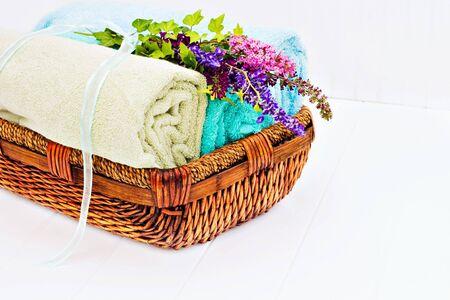 OLER ROPA LIMPIA: Cesta de lavandería con toallas limpias frescas y un ramo de flores en un beadboard blanco.  Foto de archivo
