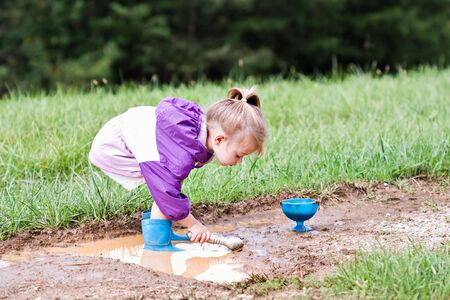 Cute little girl playing in the mud with ice cream scoops.  Stock Photo