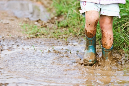 Childs feet stomping in a mud puddle.