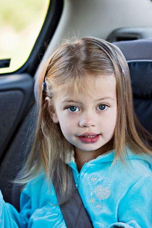 Klein meisje in een autostoeltje te kijken naar de kijker.