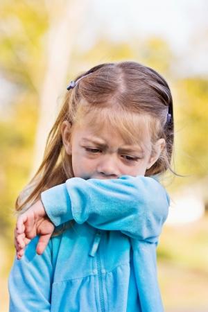 elleboog: Little girl toont aan coughing of sneezing in haar mouw te voorkomen van de verspreiding van ongewenste kiemen.  Stockfoto
