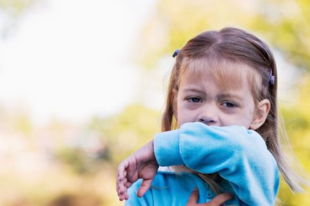 elbow sleeve: Little girl demonstrates coughing or sneezing into her sleeve to avoid spreading unwanted germs.  Stock Photo