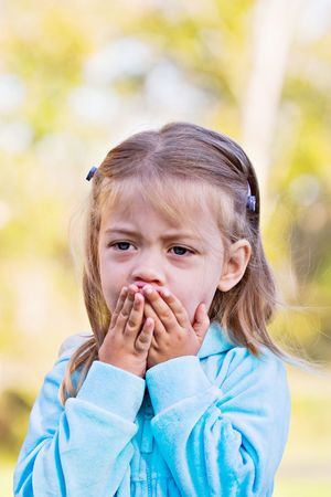 terrorized: Little girl with hands over mouth and a look of shock or sadness.  Stock Photo